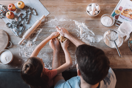 Overhead view of father and daughter kneading dough at kitchen table Stock Photo