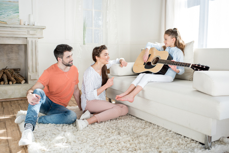 parents sitting on carpet and looking at daughter playing guitar Standard-Bild