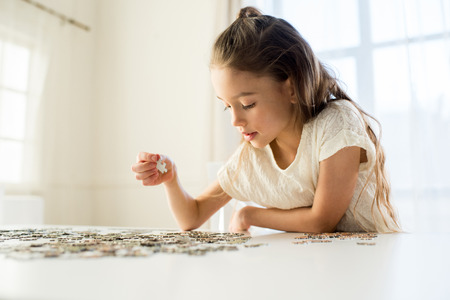 concentrated little girl playing with puzzles at home