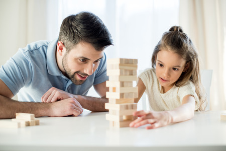 focused daughter playing jenga game with father at home Reklamní fotografie