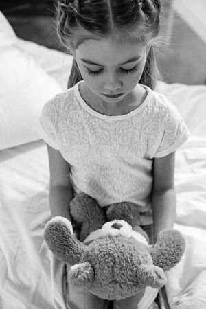upset girl with teddy bear in hospital chamber