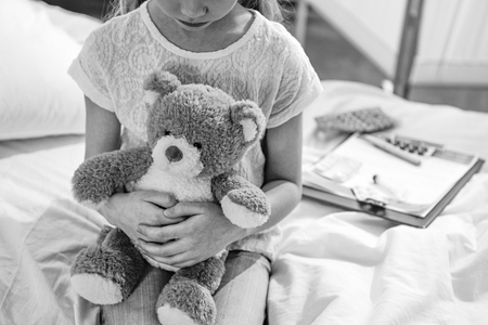 girl with teddy bear in hospital chamber, black and white photo