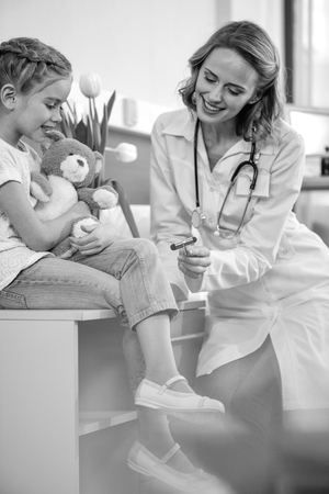 pediatrist: side view of smiling doctor examining girl with reflex hammer