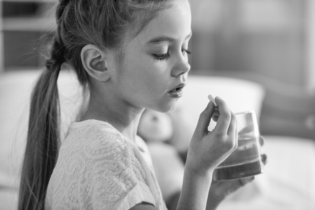 Cute little girl holding glass of water and pill Stock Photo