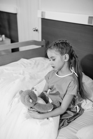 Serious little girl with teddy bear sitting on hospital bed