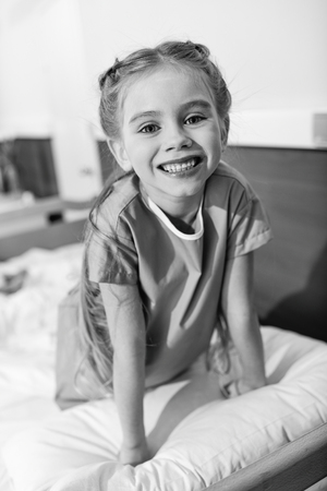 Cute little girl sitting on hospital bed and smiling at camera