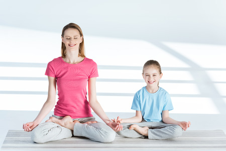 mother and daughter sitting on yoga mat in lotus position and smiling at camera