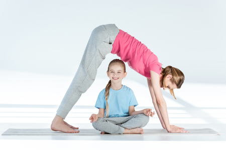 gyan: Mother practicing yoga above smiling daughter sitting in lotus position Stock Photo