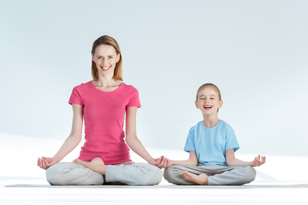 gyan: mother and daughter sitting on yoga mat in lotus position and smiling at camera