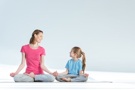 gyan: sporty mother and daughter practicing lotus position with gyan mudra asana on white Stock Photo