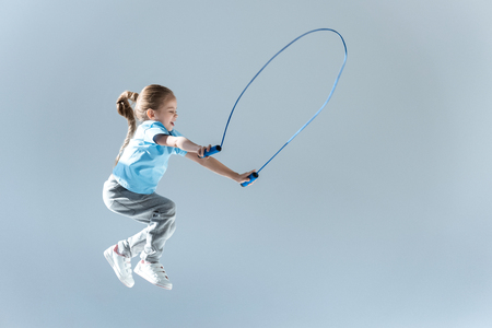 side view of happy girl humping exercising with skipping rope