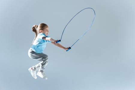 vue de côté de la fille heureuse bosse exercice avec corde à sauter Banque d'images