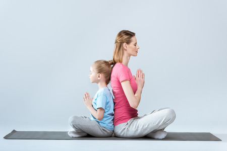 Side view of sporty mother and daughter practicing lotus yoga pose and namaste gesture together Reklamní fotografie