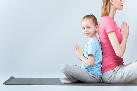 Side view of sporty mother and daughter practicing lotus yoga pose and namaste gesture together Stock Photo