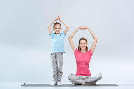 smiling sporty mother and daughter practicing yoga together Reklamní fotografie