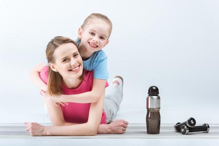 Fille souriante étreignant la mère après l'entraînement sur le blanc