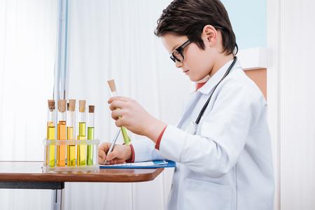 focused boy doctor analyzing test tube in hospital