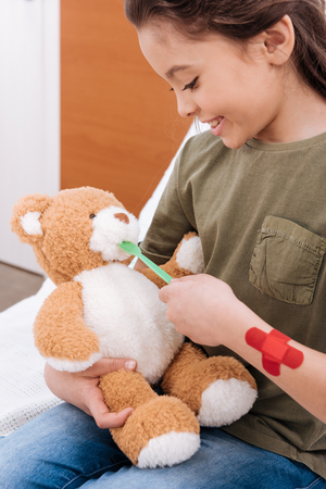 smiling girl playing doctor and patient with teddy bear
