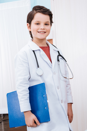 boy doctor with stethoscope holding folder and smiling at camera