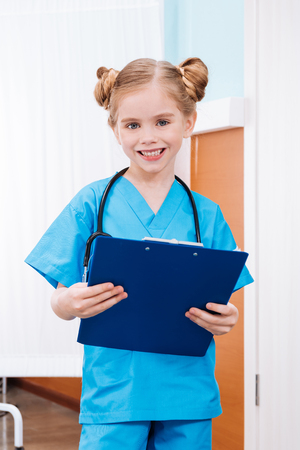 smiling girl nurse holding clipboard in hospital chamber