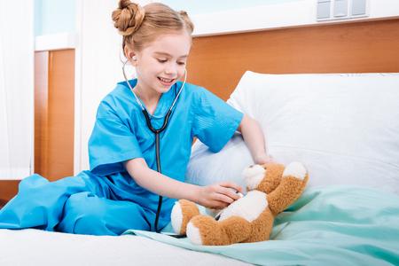 Lächelnde Mädchen Krankenschwester hören Teddybären Herzschlag mit Stethoskop Standard-Bild - 75206629