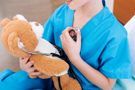 girl nurse listening heartbeat with teddy bear as doctor