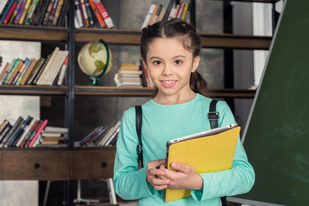 schoolgirl with backpack holding digital tablet and smiling at camera