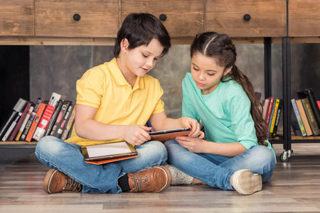 boy teaching focused girl how to use digital tablets 版權商用圖片
