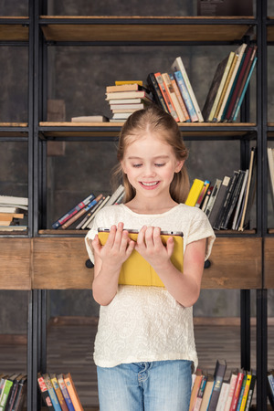 smiling girl using digital tablet in library