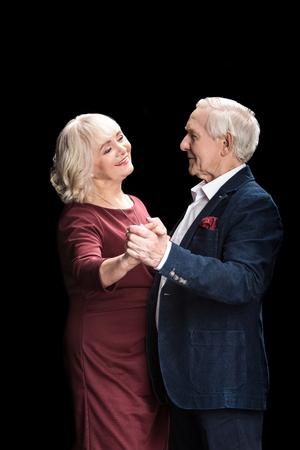 beautiful happy senior couple dancing on black