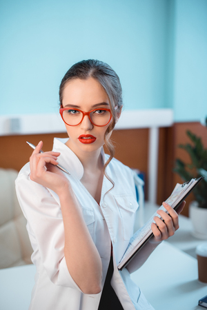 confident professional doctor in white coat and glasses holding notepad Stok Fotoğraf