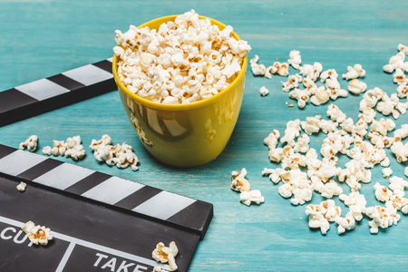 popcorn and movie clapper on wooden table, Movie time concept