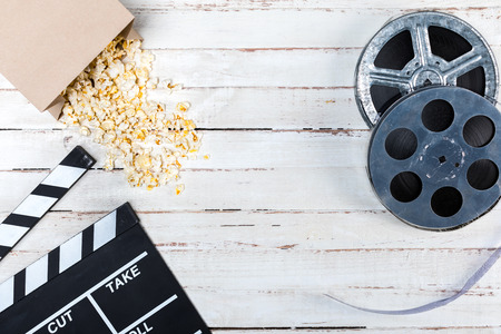 Top view of film reels, popcorn and movie clapper on wooden table Banco de Imagens