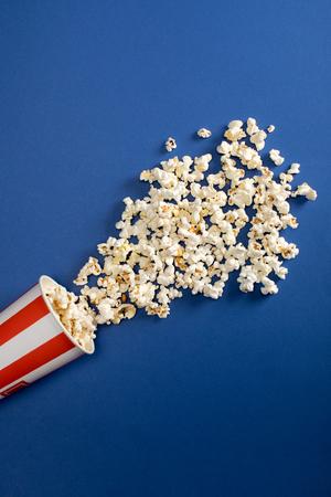 falling popcorn in box on blue background