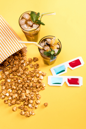glases: close up view of popcorn, iced tea and 3D glases on yellow