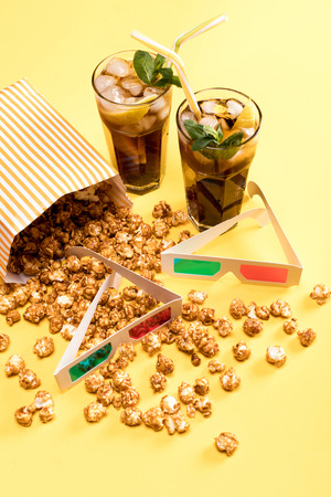 close up view of popcorn, iced tea and 3D glases on yellow