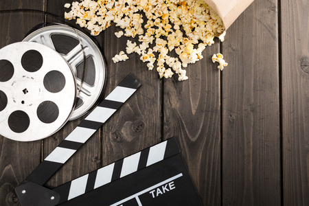 popcorn in paper container and movie clapper board on table, Movie time concept