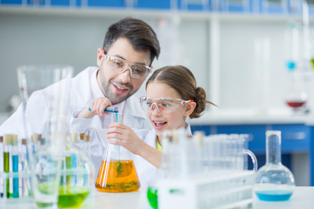 Man teacher and girl student scientists in protective glasses making experiment
