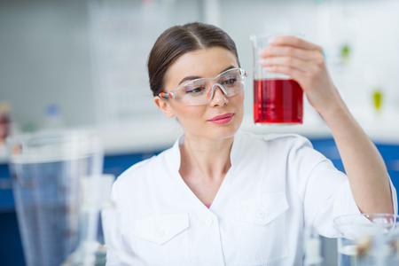 試薬とフラスコを持って防護作業服で笑顔の女性科学者