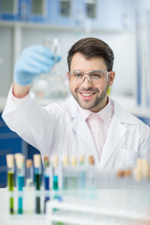 smiling scientist in protective glasses holding glass tube