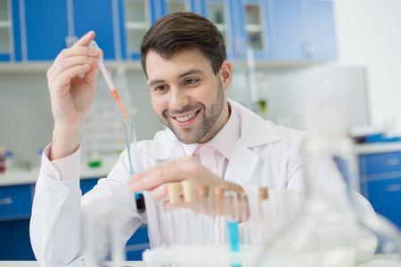 笑顔の男科学者が研究室で試験管を使用