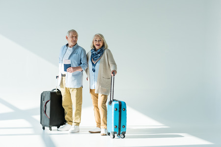 happy senior couple with traveling bags, passports and tickets