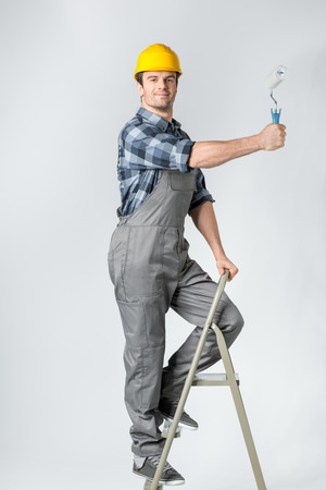 architect tools: Workman with paint roller Stock Photo