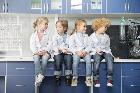 一緒に座っている白衣の小学生 写真素材