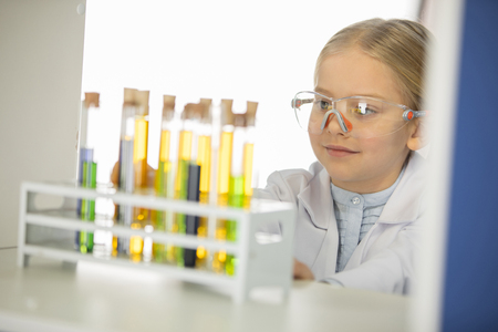 Schoolgirl in protective goggles looking at test tubes