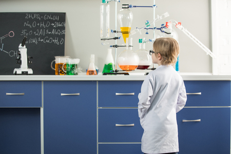 little boy wearing lab coat in science laboratory Stock fotó