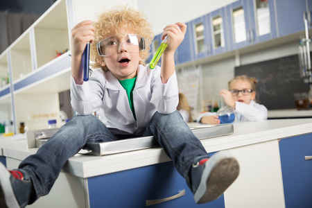 boy sitting in sink in science laboratory and holding test tubes with reagents