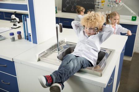 科学実験室の流しに座っている少年