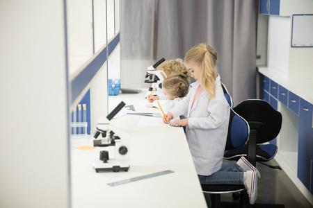 小さな子供たちの白衣を着ていると勉強 写真素材