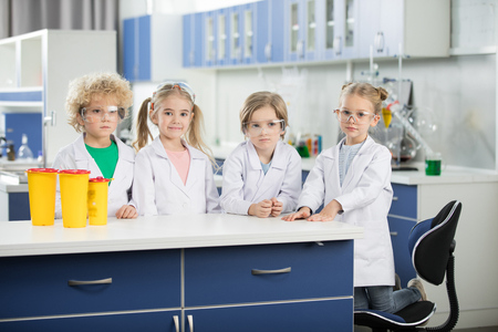 kids in science laboratory wearing coats and standing at table